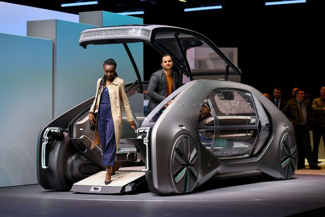 People visit the autonomous urban concept car Renault EZ-GO during the first press day of the Geneva International Motor Show on March 6, 2018 in Geneva. The show opens to the public on March 8 and runs through March 18. (Photo by Fabrice Coffrini/AFP Photo)
