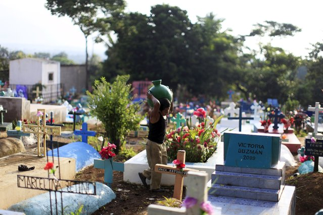 A man carries water to clean the grave of a relative during celebration of the Day of the Dead in Nahuizalco, El Salvador November 2, 2015. (Photo by Jose Cabezas/Reuters)