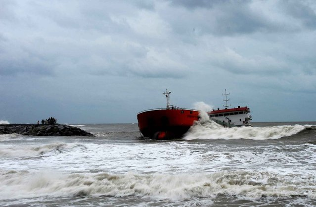 This picture taken on December 18, 2014 shows residents watching as an Indonesia-registered tanker lies in rough sea close to the shore after it was pushed by strong winds during stormy weather in the Thai southern city of Narathiwat. Parts of southern Thailand have experienced floods in recent days after heavy rains hit the region. (Photo by Madaree Tohlala/AFP Photo)