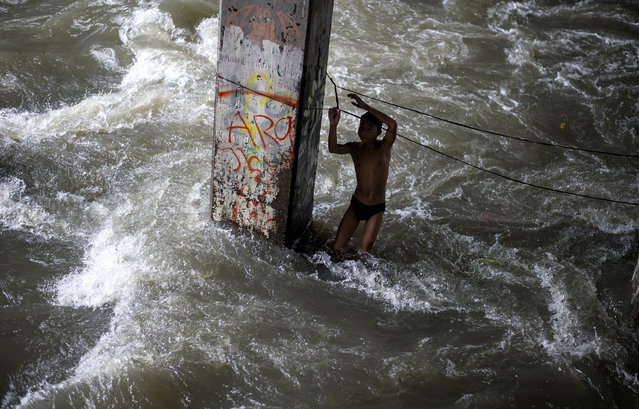 A boy plays in a swollen creek under a bridge in Manila on October 16, 2016. Typhoon Sarika lashed the main Philippine island of Luzon on October 16, flattening homes and toppling trees and power pylons as more than 12,000 people fled to safer ground, officials said. Shanties built beside a river, under a creek are the usual victims of floodings. (Photo by Noel Celis/AFP Photo)