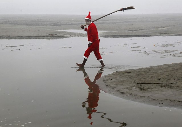 A Hindu devotee wearing a Santa Claus costume walks after cleaning a part of the banks of the river Ganges in the northern Indian city of Allahabad December 23, 2014. (Photo by Jitendra Prakash/Reuters)