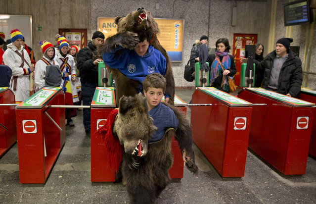 Children from Dofteana, northern Romania, some wearing bear furs, enter a subway station on their way to the city center, to perform a holiday season ritual in Bucharest, Romania, Tuesday, December 23, 2014. (Photo by Vadim Ghirda/AP Photo)