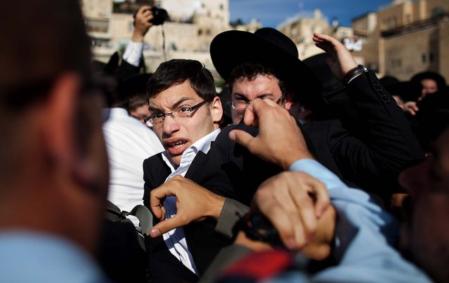 """Ultra-Orthodox protesters clash with Israeli police officers during the prayer service held by the """"Women Of The Wall"""", on May 10, 2013. (Photo by Uriel Sinai/Getty Images)"""