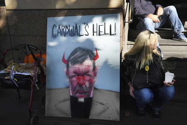 A demonstrator sits beside a placard carrying the image of Australian Cardinal Greorge Pell, outside the Melbourne Magistrate Court in Melbourne Tuesday, May 1, 2018. Australian Cardinal Pell, the most senior Vatican official to be charged in the Catholic Church s*x abuse crisis, must stand trial on charges that he sexually abused multiple victims decades ago, a magistrate ruled Tuesday. (Photo by Andy Brownbill/AP Photo)