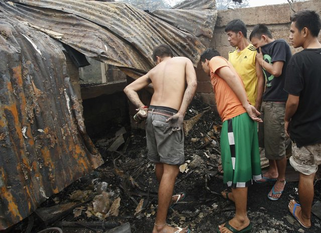 Residents look at a charred body killed by a fire at a slum colony in Quezon city, Metro Manila January 1, 2015. (Photo by Erik De Castro/Reuters)