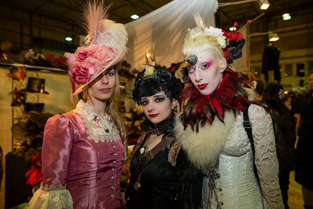 Three girls in Victorian clothing pose for pictures at the Agra festival area on the first day of the annual Wave-Gotik Treffen, or Wave and Goth Festival, on May 17, 2013 in Leipzig, Germany. The four-day festival, in which elaborate fashion is a must, brings together over 20,000 Wave, Goth and steam punk enthusiasts from all over the world for concerts, readings, films, a Middle Ages market and workshops. (Photo by Marco Prosch)