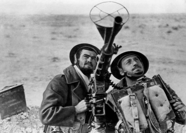 """Two soldiers of the """"Free French"""" armies man a captured Italian anti-aircraft gun in the siege of Bardia, eastern Libya on January 26, 1941. The British credited the """"Free French"""" with important aid in the Libyan campaign. (Photo by AP Photo)"""
