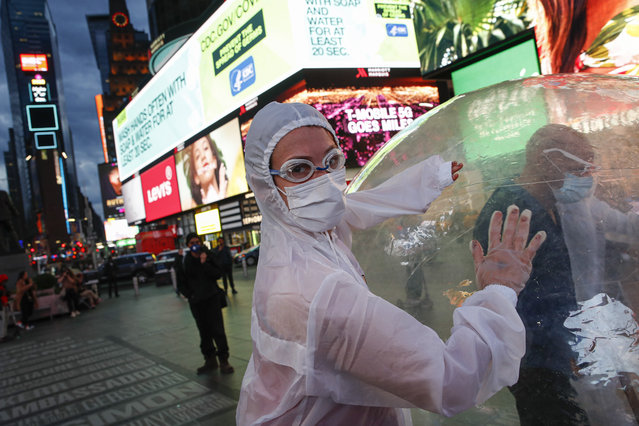 """Artists perform under a billboard displaying information on COVID-19 in a sparsely populated Times Square, Friday, March 20, 2020, in New York. New York Gov. Andrew Cuomo is ordering all workers in non-essential businesses to stay home and banning gatherings statewide. """"Only essential businesses can have workers commuting to the job or on the job"""", Cuomo said of an executive order he will sign Friday. Nonessential gatherings of individuals of any size or for any reason are canceled or postponed. (Photo by John Minchillo/AP Photo)"""
