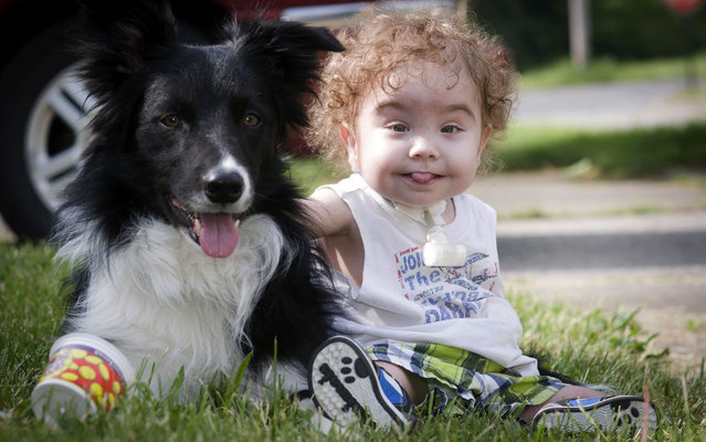 Kaiba Gionfriddo plays with Bandit, the family dog, outside his Youngstown, Ohio, home, on May 23, 2013. (Photo by Mark Stahl/AP Photo)