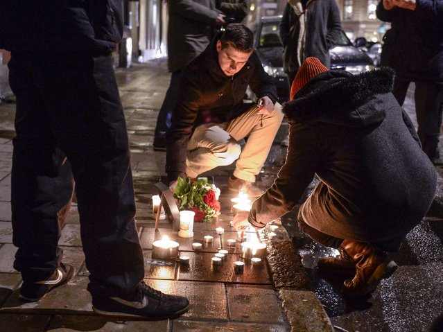 People light candles in tribute to the victims of a shooting by gunmen at the offices of weekly satirical magazine Charlie Hebdo in Paris, outside the French embassy in Stockholm, January 7, 2015. (Photo by Claudio Bresciani/Reuters/TT News Agency)