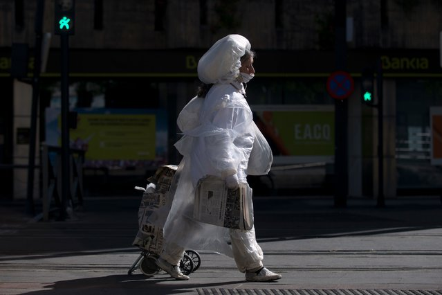A woman covered in plastic film walks in Granada on May 2, 2020. All Spaniards are again allowed to leave their homes since today to walk or play sports after 48 days of very strict confinement to curb the coronavirus pandemic. After allowing children under 14 to go out since April 26, the government has again eased the conditions of the confinement imposed on March 14, which was one of the strictest in the world. (Photo by Jorge Guerrero/AFP Photo)