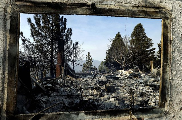 A window frames the view of one of at least five structures destroyed or severely damaged in Lake Hughes. Erratic wind fanned a blaze in the Angeles National Forest to nearly 41 square miles on June 2, 2013, after fast-moving flames triggered the evacuation of nearly 1,000 homes in Lake Hughes and Lake Elizabeth. (Photo by Reed Saxon/Associated Press)