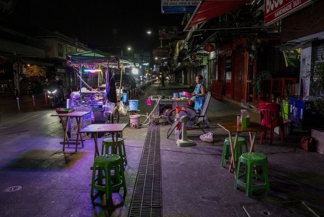 A lone street vender waits for customers at Khao San road, a once popular hangout with bars and entertainment for locals and tourists in Bangkok, Thailand, Monday, January 4, 2021. Thailand on Tuesday, Jan. 5, 2021, reported over 500 new coronavirus cases, most of them migrant workers who already were isolated, and the government said it was tightening movements of people around the country. (Photo by Gemunu Amarasinghe/AP Photo)