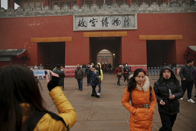 People leave the Forbidden City on an extremely polluted day as hazardous, choking smog continues to blanket Beijing, China December 1, 2015. (Photo by Damir Sagolj/Reuters)