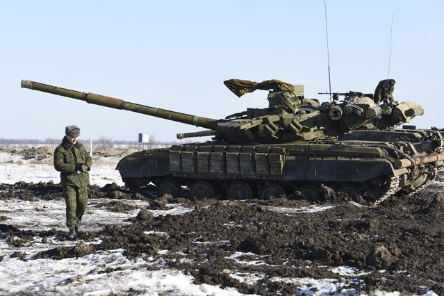 In this Wednesday, January 14, 2015 photo Russian-backed separatist walks past tanks at the check-point north of Luhansk, Eastern Ukraine. An attack on a passenger bus in eastern Ukraine killed 12 people Tuesday, likely dealing the final blow to hopes that a short-lived and shaky cease-fire could take hold. (Photo by Mstyslav Chernov/AP Photo)