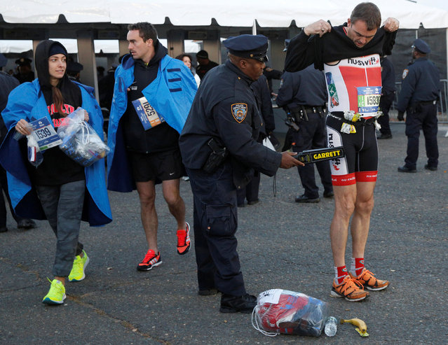 NYPD officers check runners as they arrive to compete in the 2016 New York City Marathon in the Manhattan borough of New York City, U.S., November 6, 2016. (Photo by Brendan McDermid/Reuters)