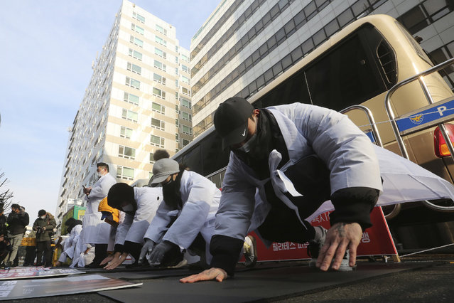 Members of Plates and Fitness Business Association bow during a rally demanding the government to allow the reopening of their businesses amid tightened social distancing rules against the pandemic in front of the ruling Democratic Party headquarters in Seoul, South Korea, Tuesday, January 12, 2021. South Korean President Moon Jae-in on Monday said the government will offer COVID-19 vaccinations to everyone free of charge in phased steps. (Photo by Ahn Young-joon/AP Photo)
