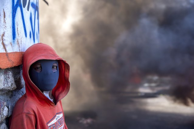 A masked protester stands near a burning barricade during a protest to demand the resignation of Haitian President Jovenel Moise in Port-au-Prince, Haiti, Sunday, February 7, 2021. (Photo by Dieu Nalio Chery/AP Photo)