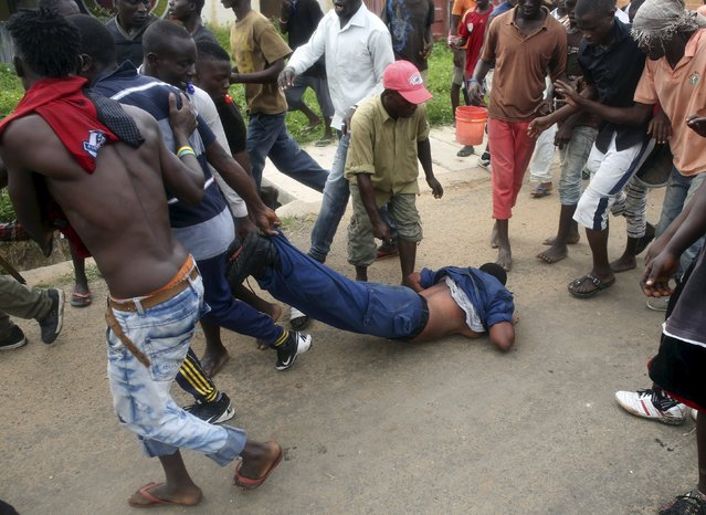 Protesters drag a female police officer accused of shooting a protester in the Buterere neighbourhood of Bujumbura, Burundi, May 12, 2015. (Photo by Goran Tomasevic/Reuters)