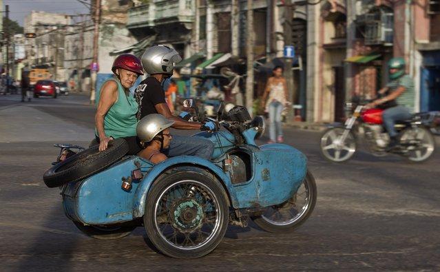 In this October 8, 2014, file photo, people ride in an Ural Soviet motorcycle in Havana, Cuba. (Photo by Franklin Reyes/AP Photo)