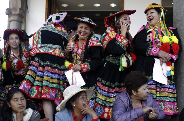 Women dancers laugh after performing in Cuzco, Peru, Saturday, June 23, 2018. June is full of festivities throughout the region of Cuzco, culminating on June 24 with the Inti Raymi, the Festival of the Sun. (Photo by Martin Mejia/AP Photo)