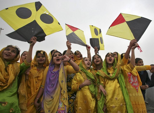 Schoolgirls wearing colourful dresses cheer as they prepare to fly kites during an event to mark the Basant or spring festival in the northern Indian city of Amritsar January 23, 2015. Basant is celebrated mainly in the Indian states of Haryana and Punjab and marks the start of the spring season. (Photo by Munish Sharma/Reuters)