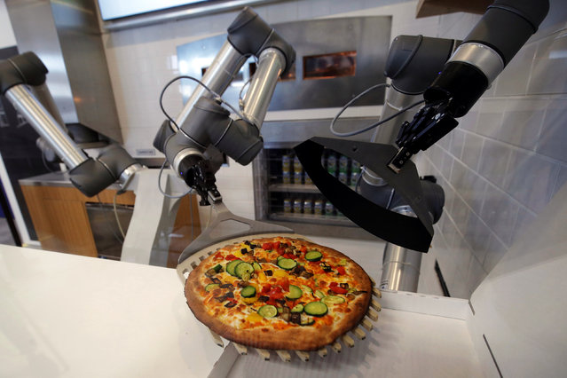 A pizzaiolo robot prepares a pizza before the customer's eyes at the showroom of French food startup EKIM in Montevrain near Paris, France, June 26, 2018. (Photo by Philippe Wojazer/Reuters)