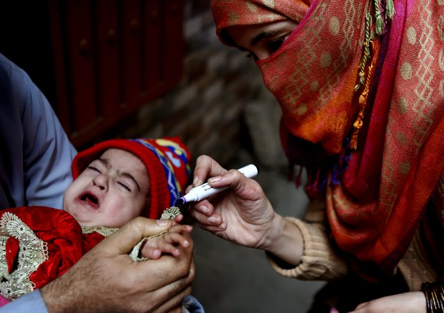 A health worker marks fingers after giving polio vaccinations to child, in Lahore, Pakistan, Monday, January 11, 2021. Despite a steady rise in coronavirus cases, Pakistan on Monday launched a five-day vaccination campaign against polio amid tight security, hoping to eradicate the crippling children's disease this year. (Photo by K.M. Chaudary/AP Photo)