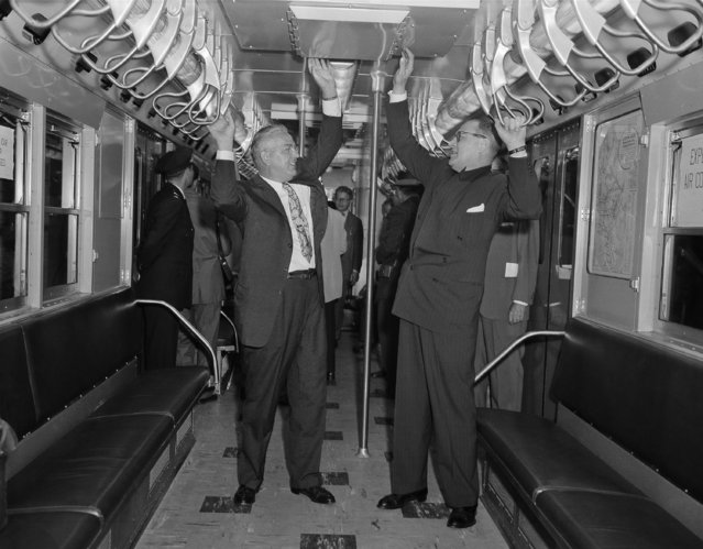 Subway commissioner Joseph E. O'Grady, left, and Transit Authority Chairman Charles L. Patterson try straphanging and feeling the cool air coming from the ceiling ducts in an air conditioned subway car, July 9, 1956. (Photo by Harry Harris/AP Photo)