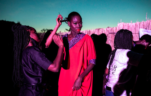 A fashion model gets the final touches done to her outfit during Dakar Fashion Week in Dakar, Senegal on December 12, 2020. (Photo by John Wessels/AFP Photo)