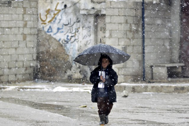 A child walks under an umbrella during a snow storm in Kvromh village in Idlib province January 15, 2015. (Photo by Khalil Ashawi/Reuters)