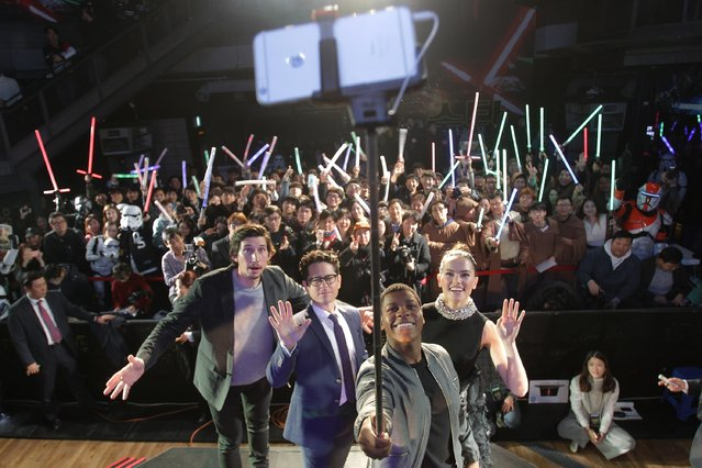 """Actor John Boyega (2nd R) takes selfie with actor Adam Driver (L) director J.J. Abrams (2nd L) and actress Daisy Ridley (R) during the event for fans ahead of """"Star Wars: The Force Awakens"""" South Korea premiere at the Octagon on December 9, 2015 in Seoul, South Korea. (Photo by Chung Sung-Jun/Getty Images for Walt Disney Studios)"""