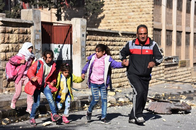 A Syrian man evacuates children from a school reportedly hit by rebel rocket fire in the Furqan neighbourhood of the government- held side of west Aleppo, on November 20, 2016. At least seven children were killed by rebel rocket fire that hit a school in the government- held west of Aleppo city, state media said. Government forces are currently waging a ferocious assault against east Aleppo, targeting it with air strikes, barrel bombs and artillery fire. (Photo by George Ourfalian/AFP Photo)