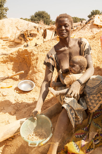 Burkina Faso, West Africa 2010. A woman and her newborn son process freshly recovered ore in the goldfields of West Africa's Burkina Faso. Work in the mines is long and hard with little differentiation between the sexes other than that the men do the mining and many women help with the processing. (Photo by Hugh Brown/South West News Service)