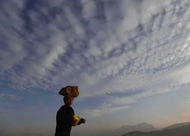 A boy carries bread on his head to sell in Kabul February 9, 2015. (Photo by Mohammad Ismail/Reuters)