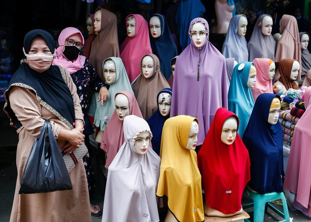 Women wearing protective masks stand next to hijabs for sale at Tanah Abang textile market amid the coronavirus disease (COVID-19) pandemic in Jakarta, Indonesia, March 16, 2021. (Photo by Ajeng Dinar Ulfiana/Reuters)