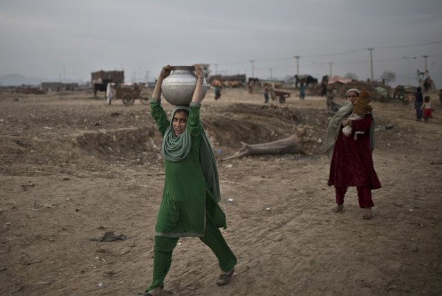 An Afghan refugee girl walks back to her family's mud home carrying water on her head in a slum on the outskirts of Islamabad, Pakistan, Friday, February 6, 2015. (Photo by Muhammed Muheisen/AP Photo)