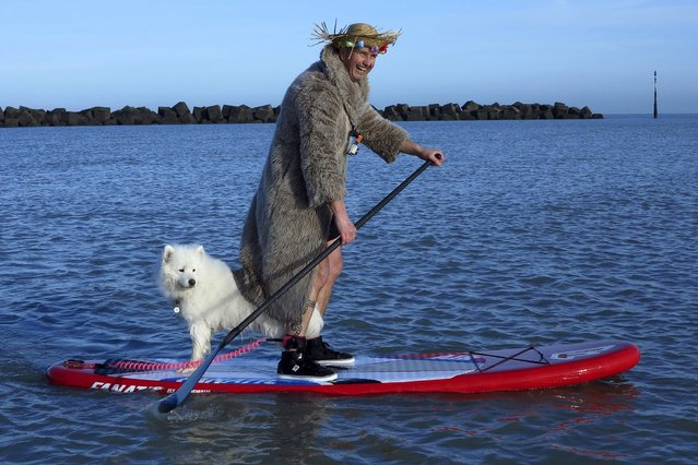 A man wearing costume paddles with a dog as he participates in a traditional New Year's Day swim in Dunkirk, northern France, January 1, 2016. (Photo by Pascal Rossignol/Reuters)