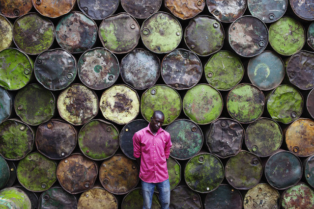 Steel barrel vendor Lassiney Diarra poses for a picture in front of barrels in Bamako August 13, 2013. (Photo by Joe Penney/Reuters)