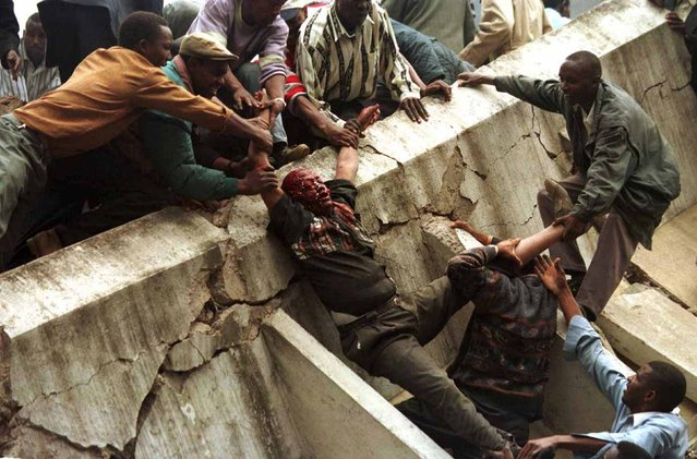 A body is removed from the wreckage after a bomb went off in Nairobi, August 7, 1998. The bomb, which killed more than 250 people and injured 5,000, was aimed at the U.S. embassy. It destroyed a neighboring building and badly damaged the embassy. (Photo by George Mulala/Reuters)
