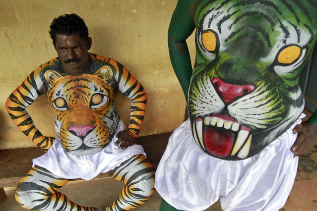 "Dancers in body paint wait to take part in a performance during festivities marking the start of the annual harvest festival of ""Onam"" in the southern Indian city of Kochi September 7, 2013. The ten-day-long Hindu festival is celebrated annually in India's southern coastal state of Kerala to commemorate the return of King Mahabali to his beloved subjects. (Photo by Sivaram V/Reuters)"