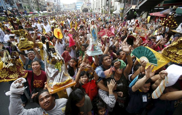 Devotees hold up religious statues as they wait to be sprinkled with holy water two days before the annual procession of the Black Nazarene in Manila January 7, 2016. (Photo by Erik De Castro/Reuters)