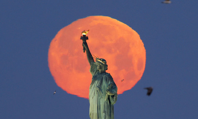 "A Pink Supermoon sets behind the Statue of Liberty in New York City on Monday, April 26, 2021. This week's supermoon is dubbed the ""pink"" moon because of its timing close to flower blooming season. (Photo by John Angelillo/UPI/Rex Features/Shutterstock)"