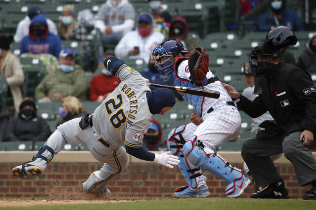 Milwaukee Brewers' Daniel Robertson (28) is hit on the head by a pitch as Chicago Cubs catcher Willson Contreras reaches for the ball during the ninth inning of a baseball game in Chicago, on Sunday, April 25, 2021. (Photo by Jeff Haynes/AP Photo)