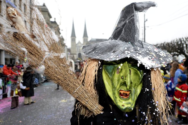 A masked reveler parades through the streets during the carnival in Lucerne, Switzerland, 16 February 2015. (Photo by Urs Flueeler/EPA)