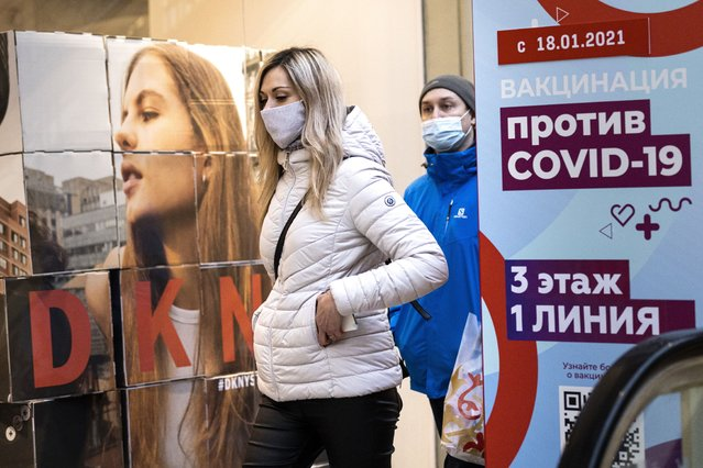 """A woman wearing a face mask to protect against coronavirus walks past a poster reading """"vaccination against COVID-19"""" at the GUM, the State Department store, near Red Square in Moscow, Russia, Wednesday, March 31, 2021. Russia has boasted about being the first country in the world to authorize a coronavirus vaccine and rushed to roll it out earlier than other countries, even as large-scale testing necessary to ensure its safety and effectiveness was still ongoing. (Photo by Alexander Zemlianichenko/AP Photo)"""