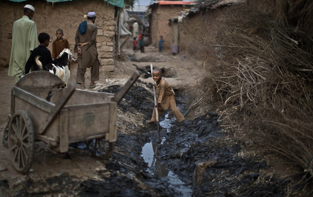 An Afghan refugee boy, center, uses a shovel to clear a sewage path outside his home in a poor neighborhood on the outskirts of Islamabad, Pakistan, Thursday, September 26, 2013. Pakistan hosts over 1.6 million registered Afghans, the largest and most protracted refugee population in the world, according to the U.N. refugee agency, thousands of them still live without electricity, running water and other basic services. (Photo by Muhammed Muheisen/AP Photo)