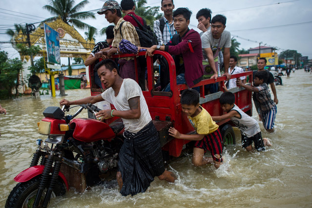 Residents push a vehicle through floodwaters in the Bago region, some 68 km away from Yangon, on July 29, 2018. Heavy monsoon rains have pounded Karen state, Mon state and Bago region in recent days and show no sign of abating, raising fears that the worst might be yet to come. (Photo by Ye Aung Thu/AFP Photo)