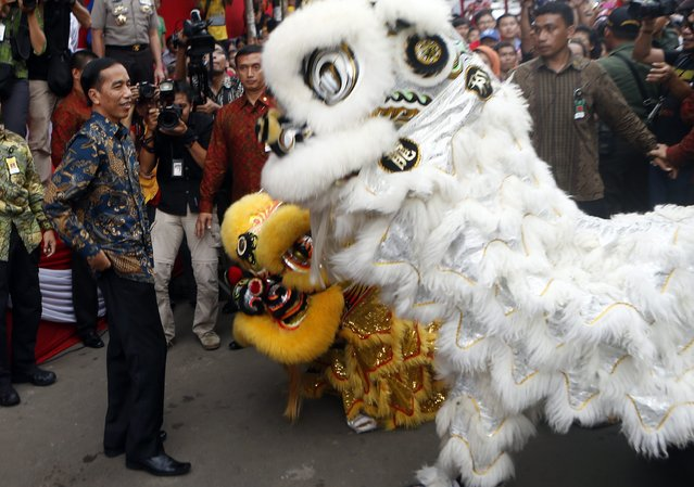 Indonesian President Joko Widodo (L) talks to lion dancers during the people's party and Chinese Cap Go Meh festival on a street in Bogor, Indonesia, 05 March 2015. Chinese-Indonesians across the country celebrate Cap Go Meh on the 15th day in the first month of the Chinese lunar New Year.  EPA/ADI WEDA