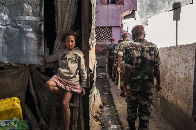 A child sit with her protective mask across her mouth and nose as members of the army patrol the streets of Antananarivo ordering citizens to go home as the Malagasy authorities declared a total weekend lockdown in the capital on April 24, 2021, to avoid the proliferation of Covid-19 which has caused many deaths in recent weeks. Madagascar said on April 23, 2021 it would receive a first lot of Covid-19 vaccines soon to fight a second wave that has overwhelmed health facilities. The Indian Ocean island nation is struggling with burgeoning infections with nearly 9,900 cases recorded over the past month, of which at least 194 have been fatal. (Photo by Rijasolo/AFP Photo)